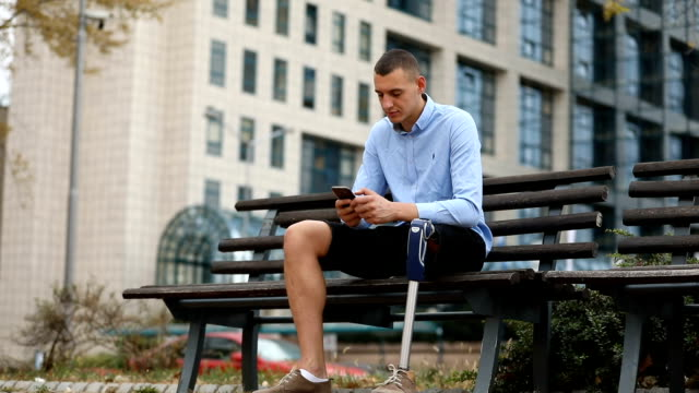 man with amputee leg using phone outdoors - amputee stock videos & royalty-free footage
