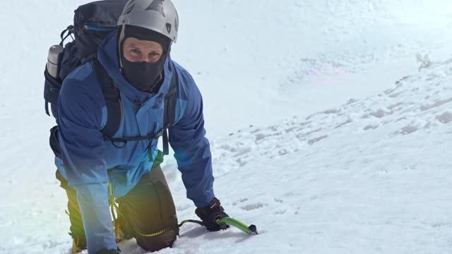 vídeos y material grabado en eventos de stock de hombre con un hacha de hielo escalando montaña nevada - nevosa