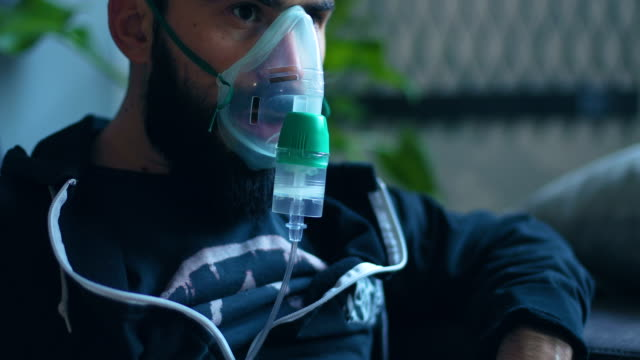 a man with an inhaler  on his face - oxygen mask stock videos & royalty-free footage