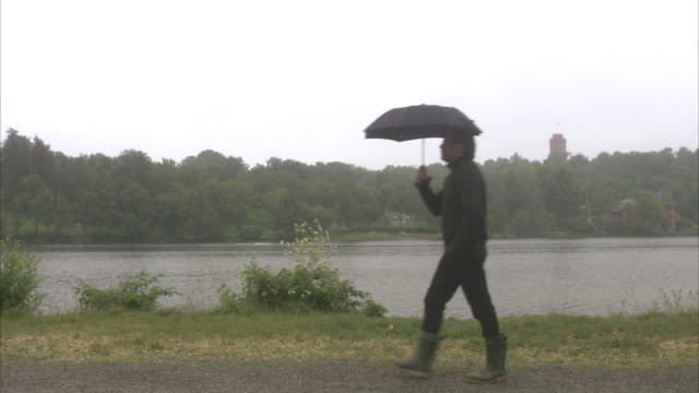A man with an umbrella walking by water, Sweden.