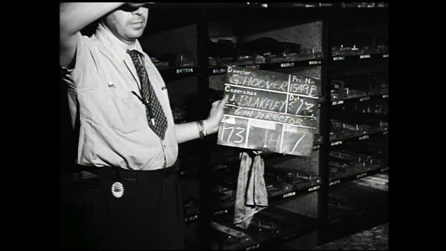 man with apron operating a metal cutter and metal being cut; man with glasses at metal assembler and working; shelves full of metal parts - 1940 1949 stock-videos und b-roll-filmmaterial