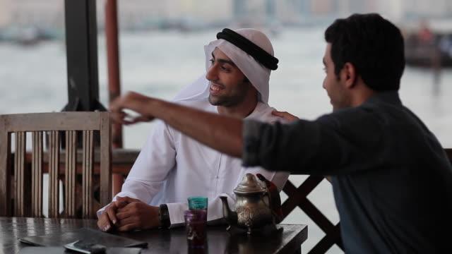 cu ms man with arab friend in outdoor restaurant/dubai/uae - only men stock videos & royalty-free footage