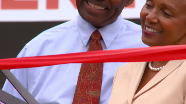 vidéos et rushes de cu td man with arm around wife as she cuts ribbon with giant scissors at grand opening of business/ ms man and woman laughing/ richmond, virginia - noeud ruban