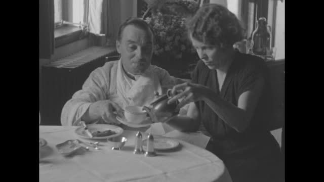 stockvideo's en b-roll-footage met man with arm in sling sitting at table in room with wife who pours him cup of tea / close shot of man drinking cup of tea / close shot of man... - drinking health 1930 film