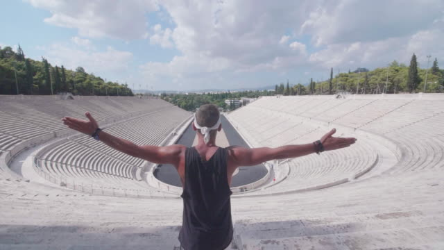 a man with arms outstretched at the panathenaic stadium in athens, greece. - panathinaiko stadium stock videos & royalty-free footage