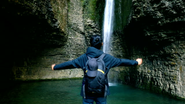 man with arms raised in front of waterfall - arms raised stock videos & royalty-free footage