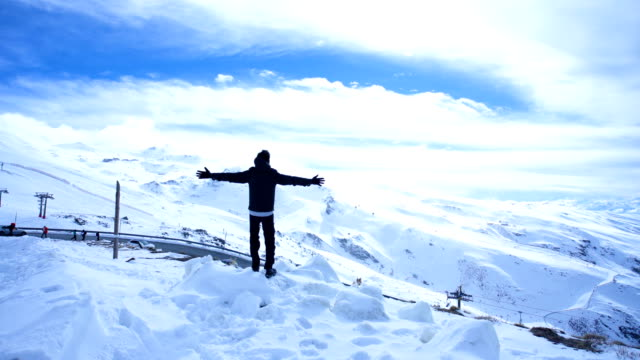Man with arms raised sees the landscape of Sierra Nevada in Spain - Snow covered mountains