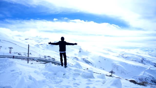 vídeos y material grabado en eventos de stock de man with arms raised sees the landscape of sierra nevada in spain - snow covered mountains - abrigo de invierno