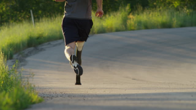 MS TU Man with artificial limb jogging on rural road / American Fork Canyon, Utah, USA