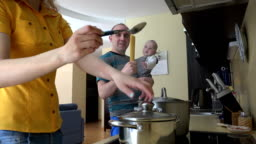 man with baby in hands and woman put spaghetti in steamy pot