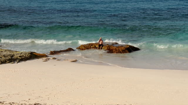 man with baby on his shoulders sitting on a rock in the sand beach in the bahamas – view from above - spoonfilm stock-videos und b-roll-filmmaterial