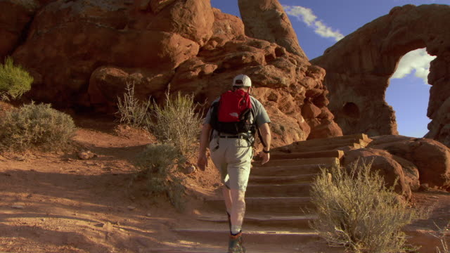 man with backpack hiking up steps on desert trail towards turret arch - red rocks stock-videos und b-roll-filmmaterial