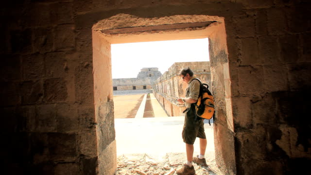 vídeos y material grabado en eventos de stock de ws man with backpack standing doorway of old ruin and using phone, uxmal, yucatan, mexico - ruina antigua