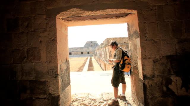 vídeos de stock e filmes b-roll de ws man with backpack standing doorway of old ruin and using phone, uxmal, yucatan, mexico - ruína antiga