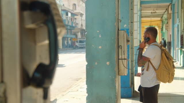 man with backpack using public phone at havana cuba street - telefonzelle stock-videos und b-roll-filmmaterial