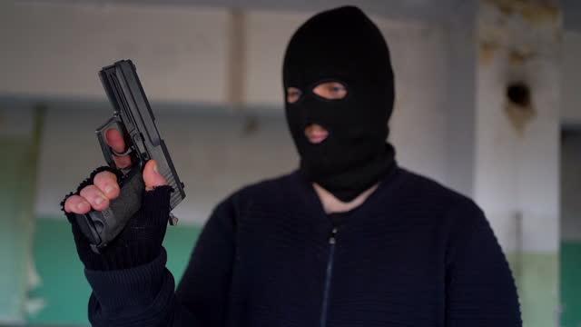 vídeos de stock e filmes b-roll de man with balaclava mask reloaded the gun - bandido