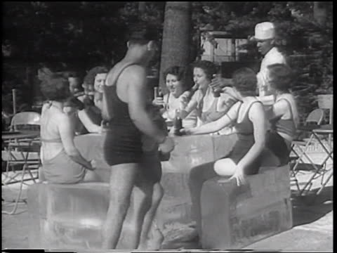B/W 1933 man with bathing suit opening cola bottles for women with bathing suits sitting on ice blocks