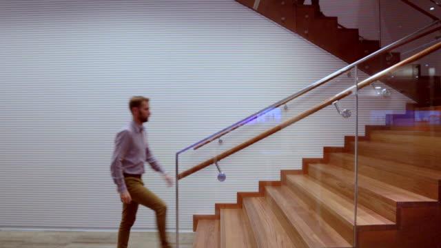 Man with beard climbing stairs inside - Stock Video