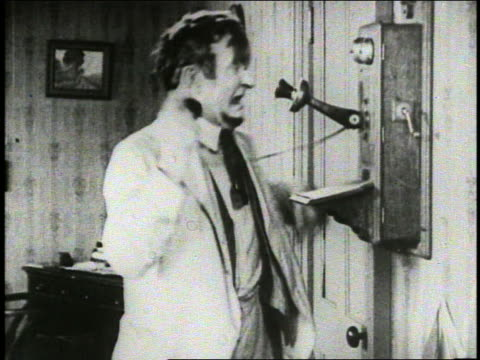 b/w 1921 man with beard (charlie murray) cranking wind-up wall telephone / silent film - 1921年点の映像素材/bロール