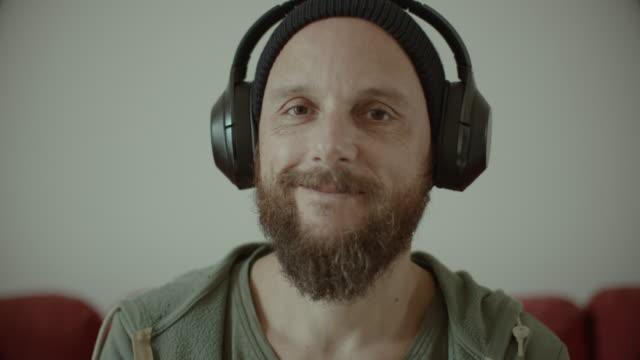 mann mit bart hört musik zu hause - zuhören stock-videos und b-roll-filmmaterial