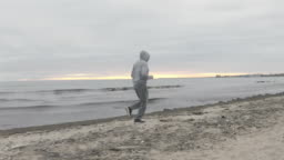 Man with Beard Running by the Beach at Dusk - Wide Dolly Shot in 4K.