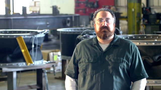 man with beard working in metal fabrication shop - barba peluria del viso video stock e b–roll