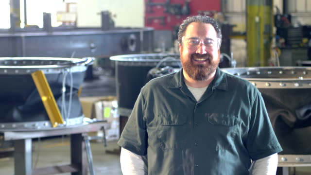 vídeos de stock e filmes b-roll de man with beard working in metal fabrication shop - 40 44 anos