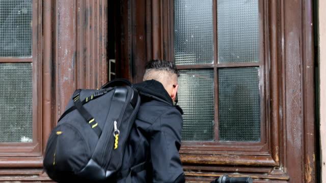 vidéos et rushes de homme avec vélo et sac à dos ouverture porte - sac à dos