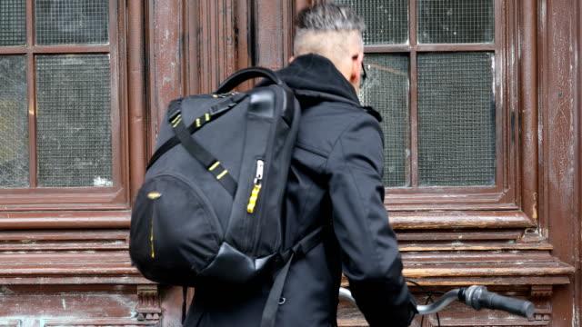 vidéos et rushes de homme avec vélo entrant par la porte en bois - sac à dos
