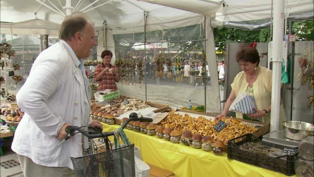 ms man with bike buying chanterelle mushrooms at viktualienmarkt, munich, bavaria, germany - chanterelle stock videos & royalty-free footage