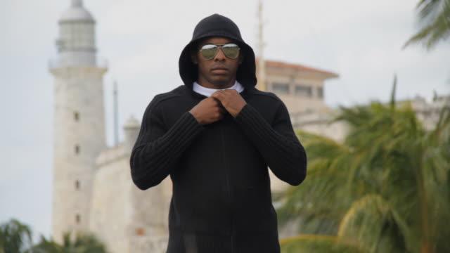 ms man with black hoodie zips his hoodie down to reveal cuban shirt / havana, cuba - black shirt stock videos & royalty-free footage