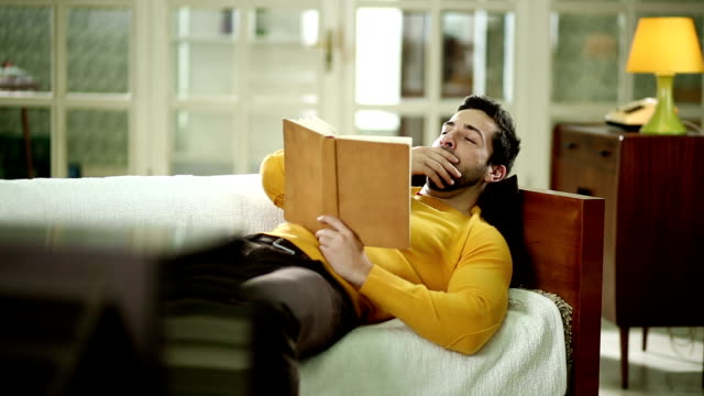 Man with book napping on the sofa