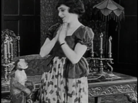1920 montage man with bouquet of flowers walking up porch steps and into house in search of his darling, who is in the house playing with a monkey - blumenbouqet stock-videos und b-roll-filmmaterial