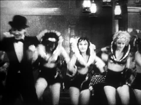 b/w 1928 pan man with bowler hat + cane dancing with chorus girls behind him / newsreel - copricapo abbigliamento video stock e b–roll
