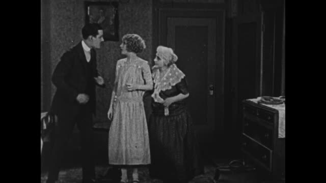 1924 man with briefcase exits house as two women watch, tips his hat, one older woman, one younger woman - silent film stock videos & royalty-free footage