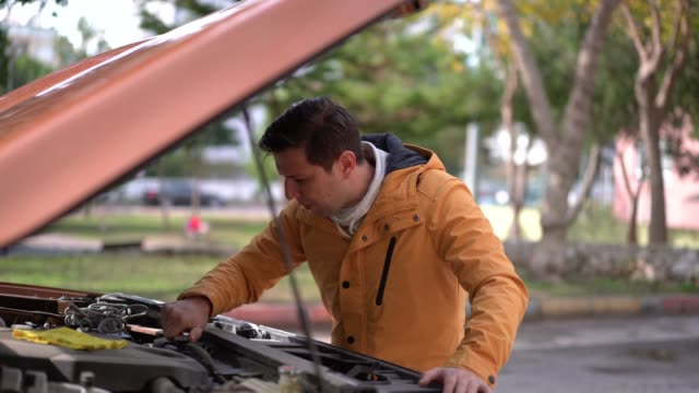vidéos et rushes de homme avec une voiture cassée vers le bas - capot de voiture