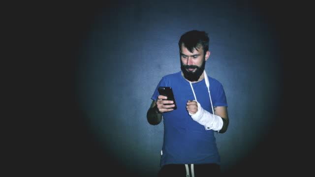 壊れた手のテキストメッセージを持つ男 - 骨折点の映像素材/bロール
