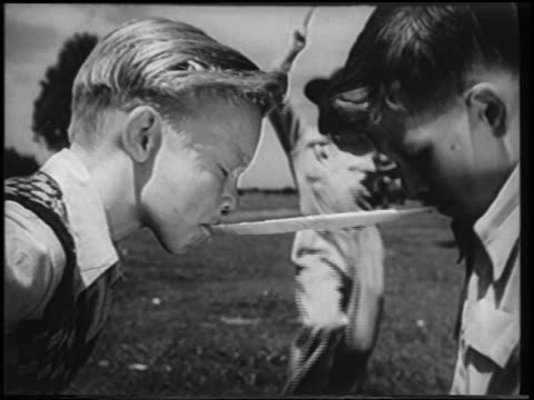b/w 1951 man with bullwhip whipping strip of paper stretched between mouths of 2 boys / newsreel - 1951 stock videos & royalty-free footage