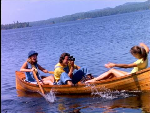 man with camera + 2 women in rowboat rocking boat on lake - 1997年点の映像素材/bロール