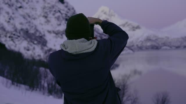 ロフォーテン島の冬に海辺を歩くカメラを持つ男 - カメラマン点の映像素材/bロール