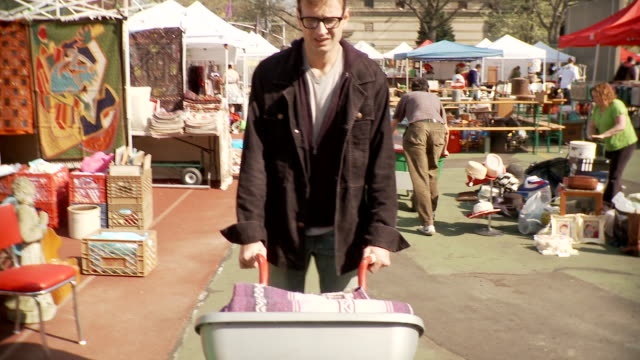 vídeos de stock, filmes e b-roll de ts ms man with cart walking through flea market, new york city, new york, usa - plano americano