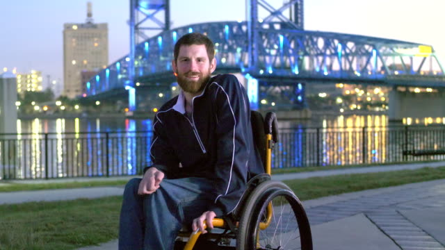 man with cerebral palsy in wheelchair on city waterfront - three quarter length stock videos & royalty-free footage