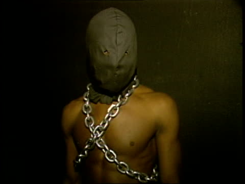 man with chains and hood in costume - anno 1985 video stock e b–roll