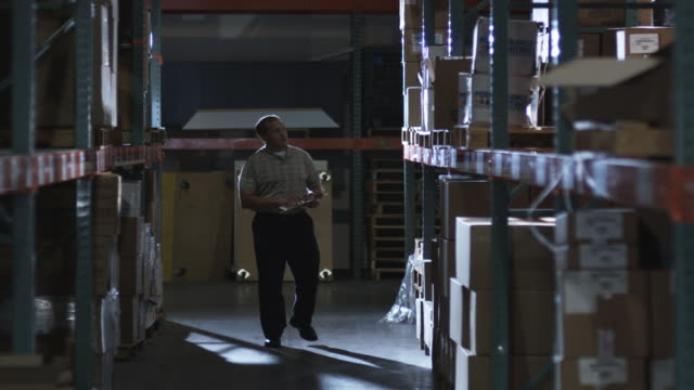 WS Man with clipboard checking warehouse inventory, Dallas, Texas, USA