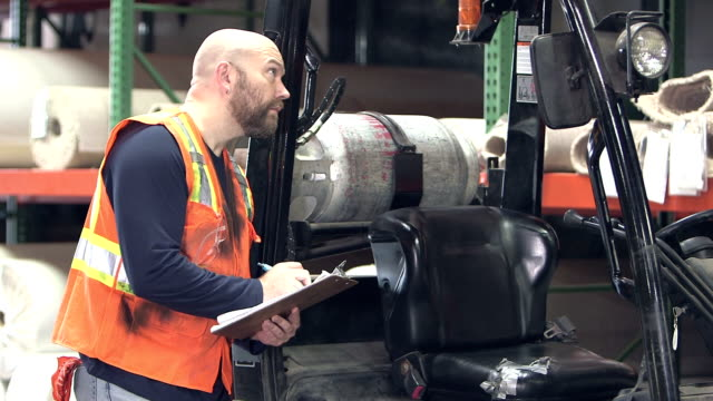 man with clipboard in warehouse, climbs on forklift - forklift truck stock videos and b-roll footage
