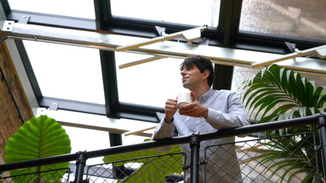 man with coffee standing on balcony with coffee in office - looking away stock videos & royalty-free footage