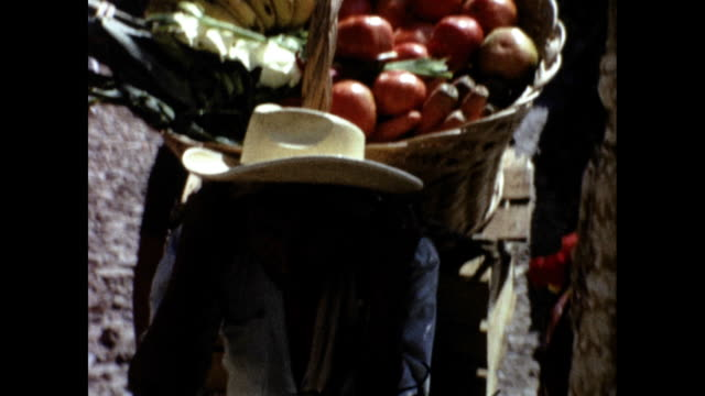 man with cowboy hat carrying basket full of fruit uphill in the sun - uphill stock videos & royalty-free footage