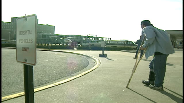 man with crutch and leg brace standing by curb - leg brace stock videos and b-roll footage