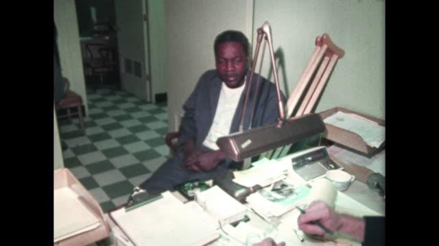 man with crutches speaks to man behind desk in office - social service bildbanksvideor och videomaterial från bakom kulisserna