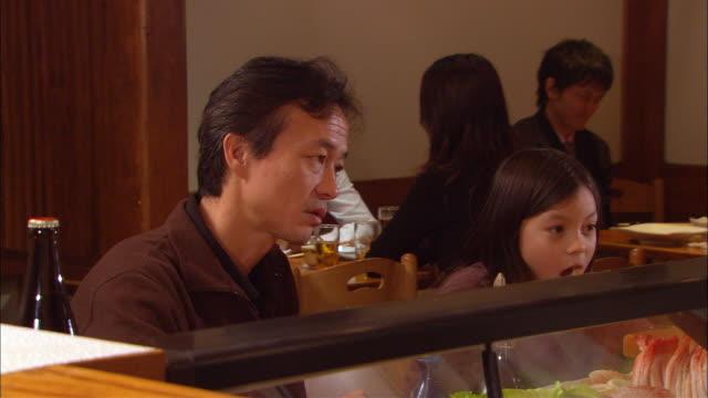 cu, man with daughter (10-11) in sushi bar - präsentation hinter glas stock-videos und b-roll-filmmaterial